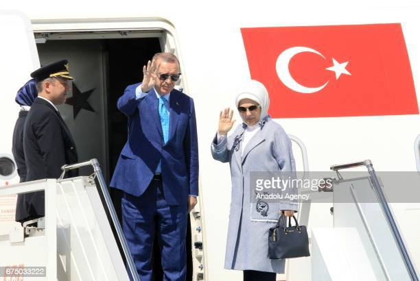 Turkish President Recep Tayyip Erdogan and his wife Emine Erdogan wave as they board the plane at Istanbul Ataturk Airport ahead of their departure...