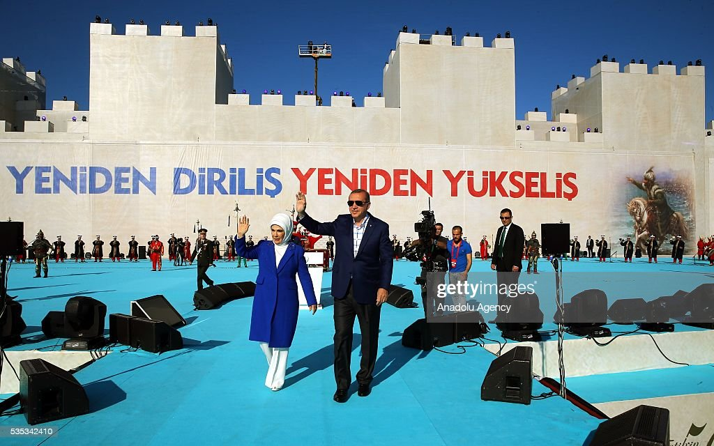 Turkish President Recep Tayyip Erdogan (R) and his wife Emine Erdogan (L) salute the participants as they walk in front of the giant model of a part of Istanbul's historical city walls with a slogan on it reading 'Again resurrection, again rising' during the celebrations of the 563rd anniversary of Istanbuls conquest by Turks at Yenikapi Event Area in Istanbul, Turkey on May 29, 2016. On May 29, 1453, Ottoman Sultan Mehmed II (Mehmet the Conqueror) conquered Istanbul, then called Constantinople, from where the Byzantines had ruled the Eastern Roman Empire for more than 1,000 years. The conquest transformed the city, once the heart of the Byzantine realm, into the capital of the new Ottoman Empire.