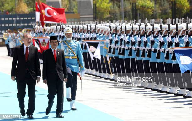 Turkish President Recep Tayyip Erdogan and Indonesian President Joko Widodo walk past honour guards during an official welcoming ceremony at the...