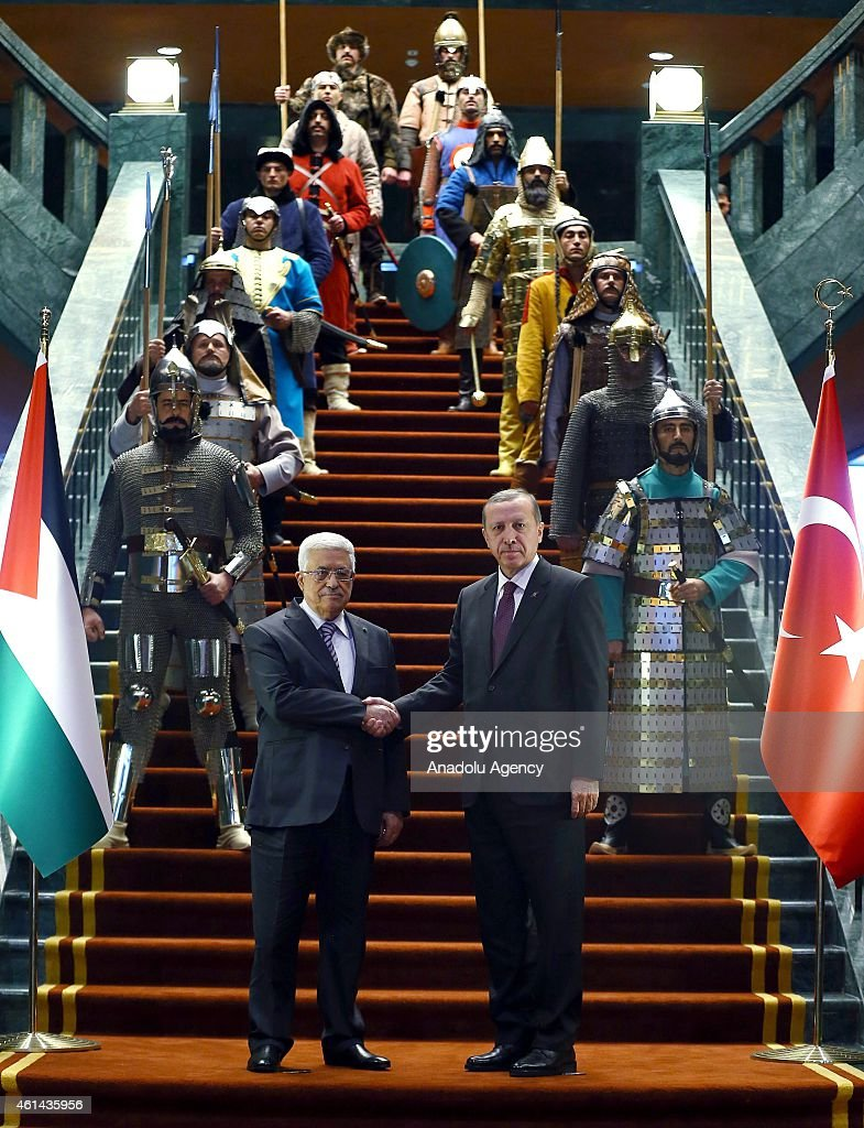 Turkish President Recep Tayyip Erdogan (R) and Palestinian President Mahmoud Abbas (L) shake hands in front of the 16 soldiers who represent the 16 Turkish states founded in the history at the Turkish presidential palace in Ankara, Turkey on January 12, 2015.
