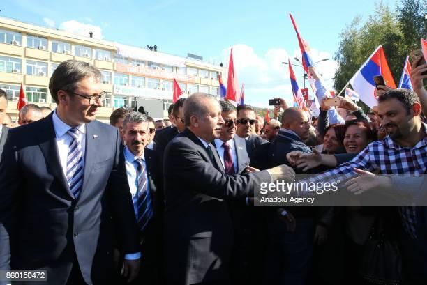 Turkish President Recep Tayyip Erdogan and Serbian President Aleksandar Vucic greet people during their visit in Novi Pazar Serbia on October 11 2017