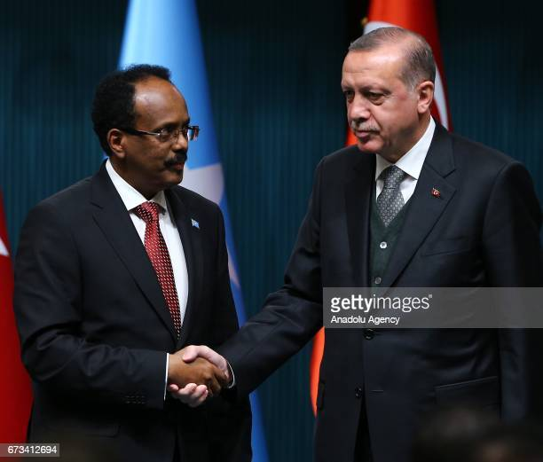 Turkish President Recep Tayyip Erdogan and Somalian President Mohamed Abdullahi Mohamed shake hands as they hold a press conference after their...