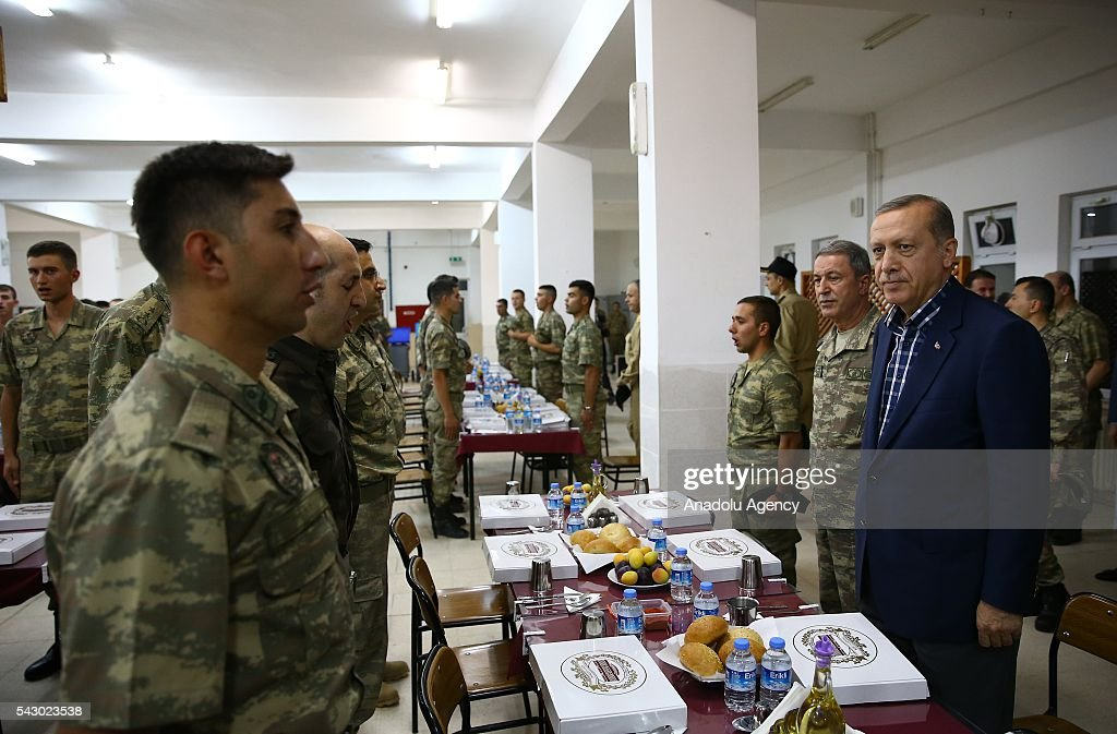 Turkish President Recep Tayyip Erdogan (R) attends an Iftar (fast-breaking) Dinner during his visit at 172. Armored Brigade Command's 3. Tank Battalion campus in Cizre District of Sirnak, Turkey on Islamic holy month Ramadan on June 25, 2016.