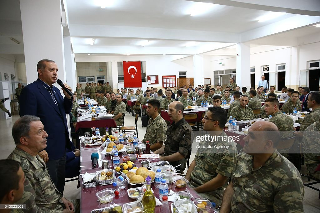 Turkish President Recep Tayyip Erdogan (3rd L) attends an Iftar (fast-breaking) Dinner during his visit at 172. Armored Brigade Command's 3. Tank Battalion campus in Cizre District of Sirnak, Turkey on Islamic holy month Ramadan on June 25, 2016.