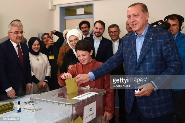 TOPSHOT Turkish President Recep Tayyip Erdogan casts his vote accompanied by his wife Emine Erdogan and their grandchildren during the referendum on...