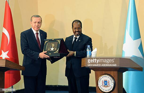 Turkish President Recep Tayyip Erdogan exchanges a plaque following a joint press conference with Somalia President Hassan Sheik Mohamud in the...