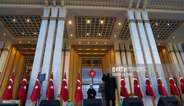 Turkish president Recep Tayyip Erdogan flanked by his wife Emine Erdogan delivers a speech to his supporters at the Presidential Palace in Ankara...