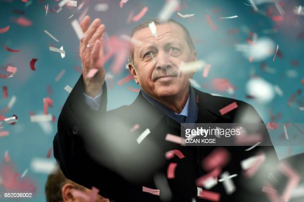 TOPSHOT Turkish President Recep Tayyip Erdogan gestures amid confetti during a rally in Istanbul on March 11 2017 Erdogan threatened to retaliate...