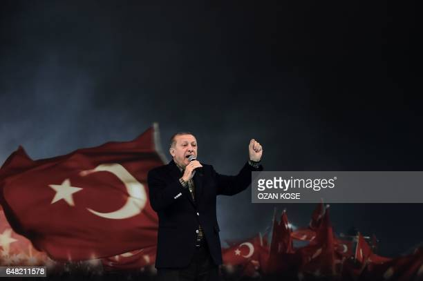 TOPSHOT Turkish President Recep Tayyip Erdogan gestures as he delivers a speech on stage on March 5 2017 in Istanbul during a progovernment women...