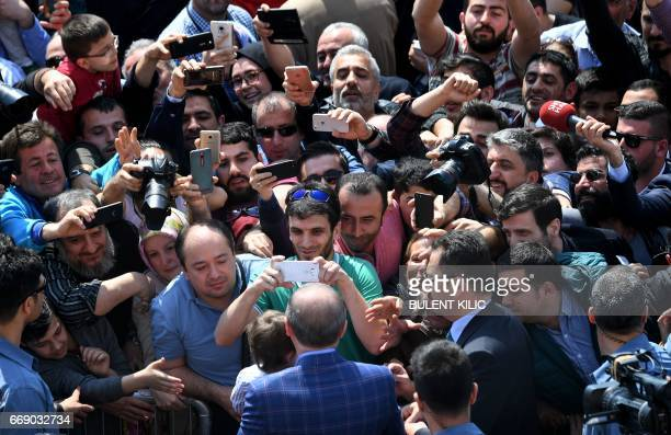 Turkish President Recep Tayyip Erdogan greets supporters as he arrives at a polling station to vote in a referendum on expanding the powers of the...
