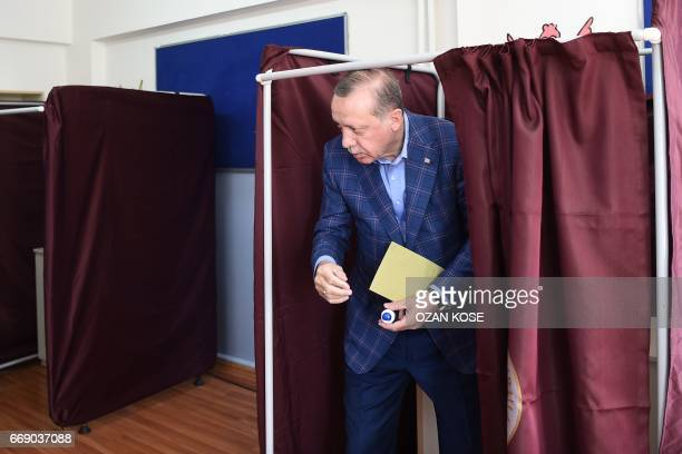 TOPSHOT Turkish President Recep Tayyip Erdogan holds his ballot as he leaves a booth to cast his vote in the referendum on expanding the powers of...