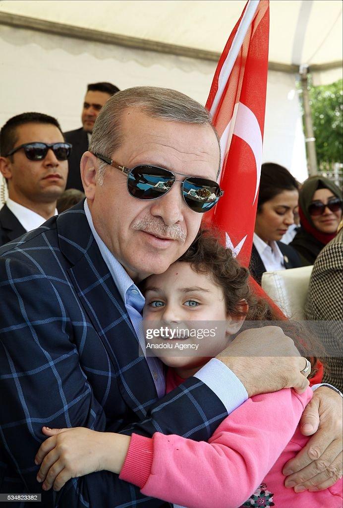 Turkish President Recep Tayyip Erdogan hugs a child during an opening ceremony in Diyarbakir, Turkey on May 28, 2016.