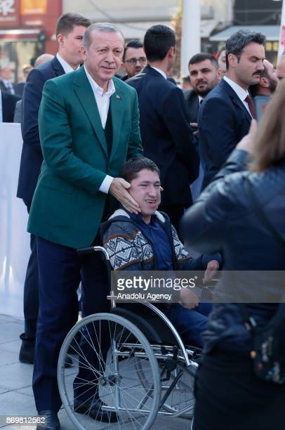 Turkish President Recep Tayyip Erdogan poses for a photo with a handicapped boy as he attends the mass opening ceremony at the Republic Square in...
