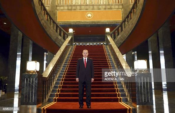 Turkish President Recep Tayyip Erdogan poses inside the new Ak Saray presidential palace on the outskirts of Ankara on October 29 2014 before hosting...