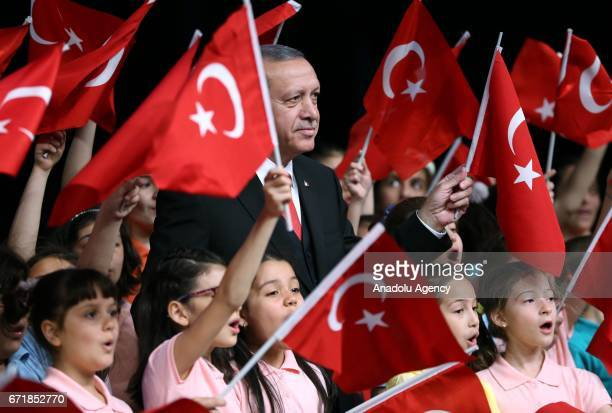 Turkish President Recep Tayyip Erdogan poses with children at Bestepe People's Culture and Congress Center during a ceremony as part of the National...