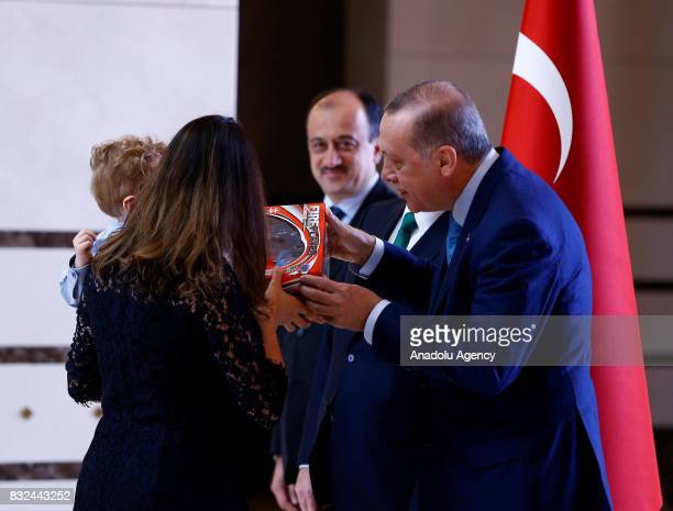 Turkish President Recep Tayyip Erdogan presents a toy to Australian Ambassador to Ankara Marc Innes Brown's child Danial as a gift at Presidential...