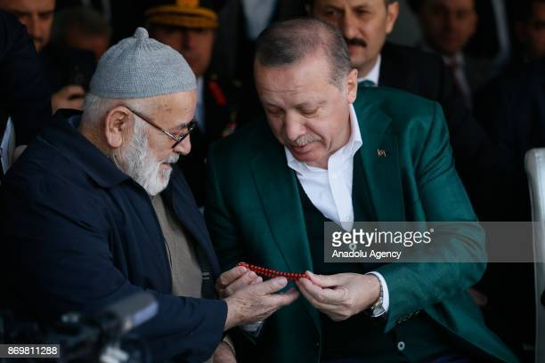 Turkish President Recep Tayyip Erdogan receives a gift from elderly couple as he attends the mass opening ceremony at the Republic Square in Manisa...