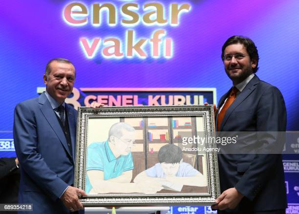 Turkish President Recep Tayyip Erdogan receives a painting from President of the Ensar Foundation Ismail Cenk Dilberoglu during the meeting of Ensar...