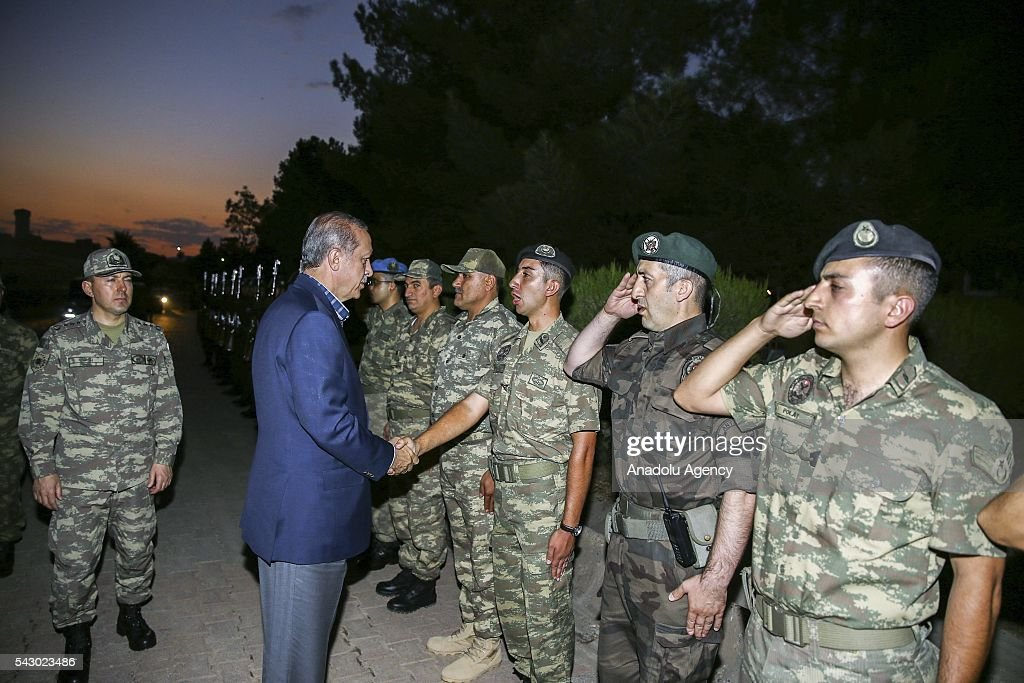 Turkish President Recep Tayyip Erdogan (2nd L) salutes soldiers as he visits 172. Armored Brigade Command's 3. Tank Battalion campus prior to an Iftar (fast-breaking) Dinner in Cizre District of Sirnak, Turkey on Islamic holy month Ramadan on June 25, 2016.
