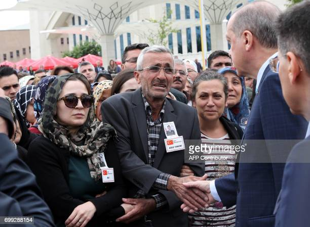 Turkish President Recep Tayyip Erdogan shakes hands with relatives as he arrives to attend the funeral of Turkish Captain Murat Ucoz who was killed...