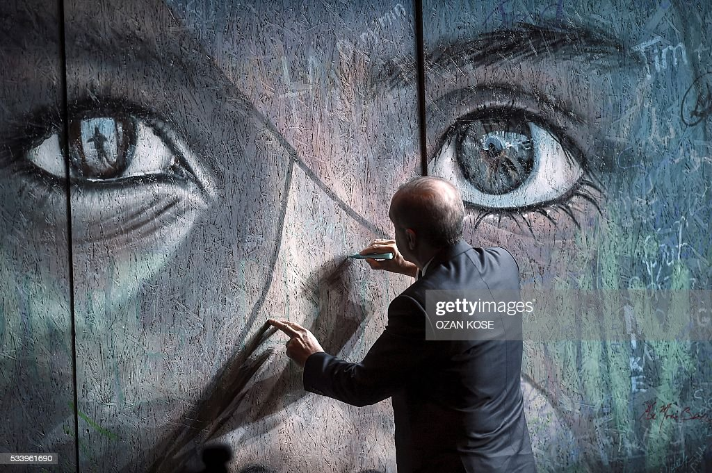 Turkish President Recep Tayyip Erdogan signs a graffiti wall during the closing cerenomy of the World Humanitarian Summit, on May 24, 2016 in Istanbul. UN Secretary General Ban Ki-moon on Tuesday said he was disappointed most top world leaders had stayed away from the first humanitarian summit in Istanbul, saying concrete political action was now needed. / AFP / OZAN