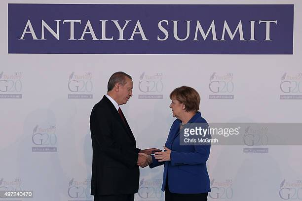 Turkish President Recep Tayyip Erdogan talks with Germany's Chancellor Angela Merkel during the official welcome ceremony on day one of the G20...
