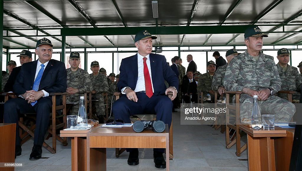 Turkish President Recep Tayyip Erdogan (C), Turkish Prime Minister Binali Yildirim (L) and Chief of the General Staff of the Turkish Armed Forces, Hulusi Akar (R) attend the Efes-2016 Combined Joint Live Fire Exercise at Seferihisar district of Izmir, Turkey on May 31, 2016. The Turkish-led multinational military exercises, Efes-2016 which started on May May 4, will be finished on June 04, 2016, aims to train participating units and staff in planning and conducting combined and joint operations, including logistics and command-control as well as to improve the level of interoperability among headquarters and forces.