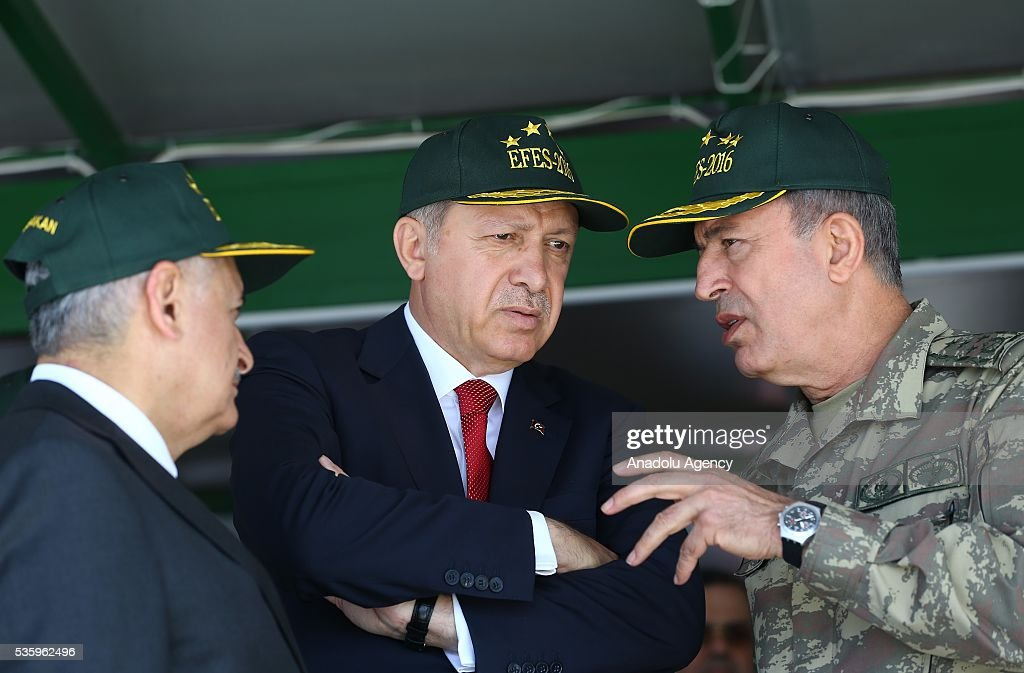 Turkish President Recep Tayyip Erdogan (C), Turkish Prime Minister Binali Yildirim (L) and Chief of the General Staff of the Turkish Armed Forces, Hulusi Akar (R) attend the Efes-2016 Combined Joint Live Fire Exercise at Seferihisar district of Izmir, Turkey on May 31, 2016. The Turkish-led multinational military exercises, Efes-2016 which started at 04 May and will be finished at 04 June 2016, aims to train participating units and staff in planning and conducting combined and joint operations, including logistics and command-control as well as to improve the level of interoperability among headquarters and forces.