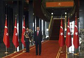 Turkish President Recep Tayyip Erdogan waits to greet guests inside the new Ak Saray presidential palace on the outskirts of Ankara on October 29...