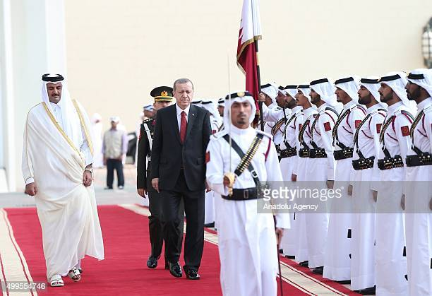 Turkish President Recep Tayyip Erdogan walks past the guard of honor after he was welcomed by the Emir of Qatar Tamim bin Hamad Al Thani during his...