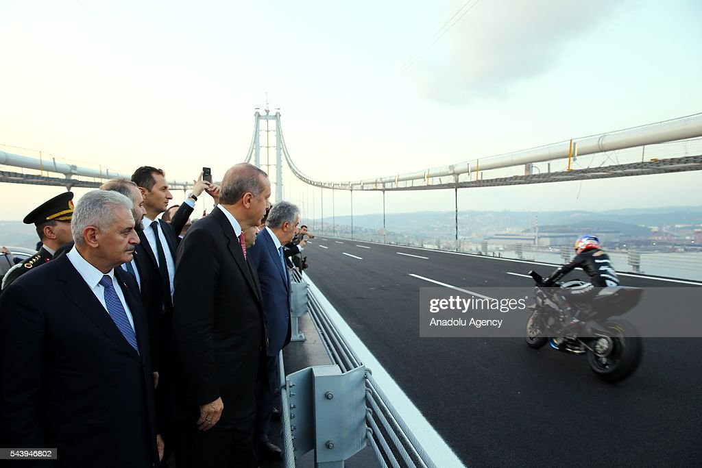 Turkish President Recep Tayyip Erdogan (C-L) watches Turkish professional motorcycle racer Kenan Sofuoglu's (R) motorcycle show during the opening ceremony of Osmangazi Bridge in Kocaeli, Turkey on June 30, 2016. Osmangazi Bridge is the fourth-longest suspension bridge in the world and second-longest bridge in Europe.
