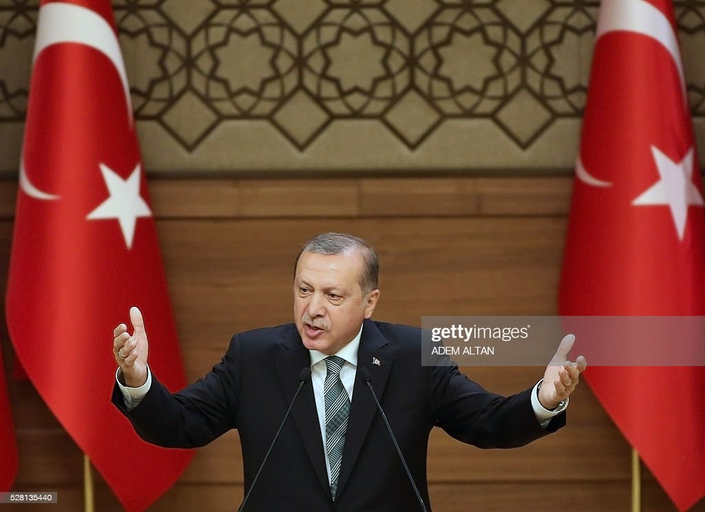 Turkish President Tayyip Erdogan gestures as he arrives to meet and speak with mukhtars or local village and town leaders at the Presidential Palace in Ankara, on May 4, 2016. / AFP / ADEM