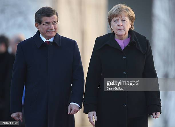 Turkish Prime Minister Ahmet Davutoglu and German Chancellor Angela Merkel walk together following Devatoglu's arrival prior to GermanTurkish...