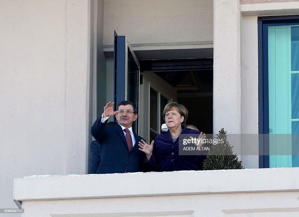 Turkish Prime Minister Ahmet Davutoglu and German Chancellor Angela Merkel gesture as they look from a balcony during their meeting in Ankara on February 8, 2016. Merkel is to hold talks with Turkey's President Recep Tayyip Erdogan and Prime Minister Ahmet Davutoglu to press Turkey to strengthen border controls to stem the flow of migrants and refugees heading for Europe. / AFP / ADEM ALTAN