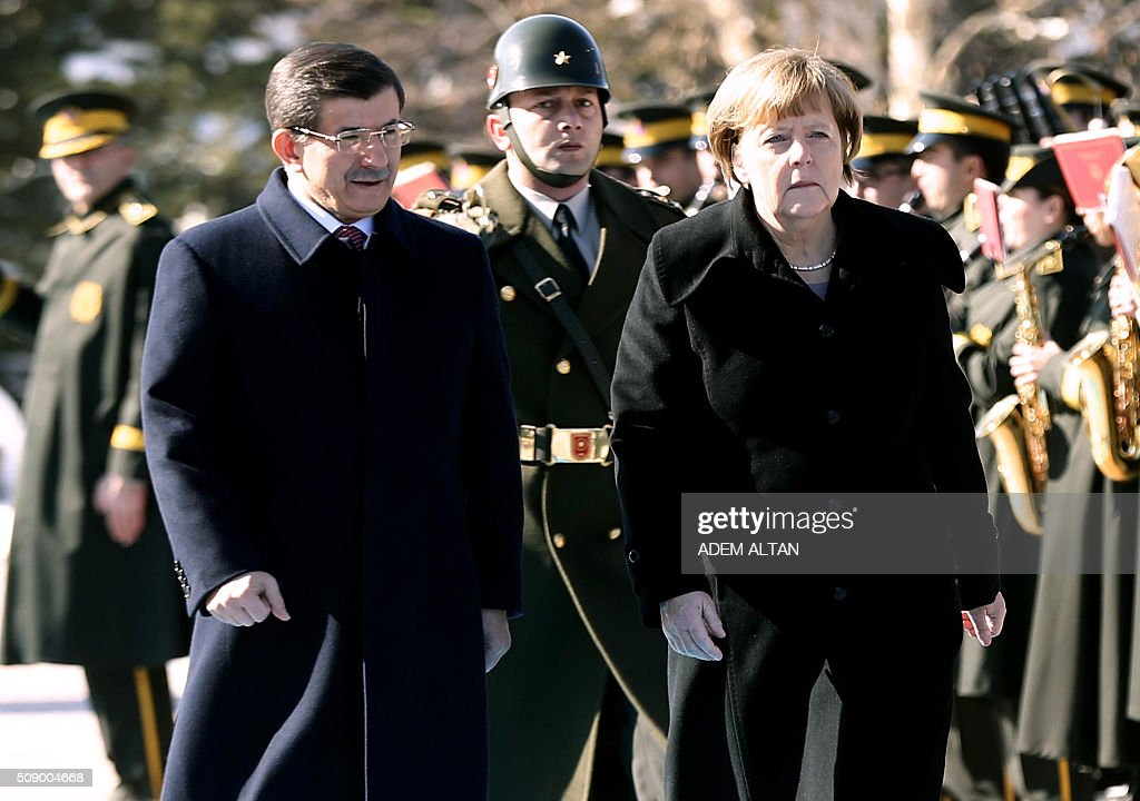 Turkish Prime Minister Ahmet Davutoglu (L) and German Chancellor Angela Merkel review a military honour guard in Ankara on February 8, 2016. Merkel is to hold talks with Turkey's President Recep Tayyip Erdogan and Prime Minister Ahmet Davutoglu to press Turkey to strengthen border controls to stem the flow of migrants and refugees heading for Europe. / AFP / ADEM ALTAN