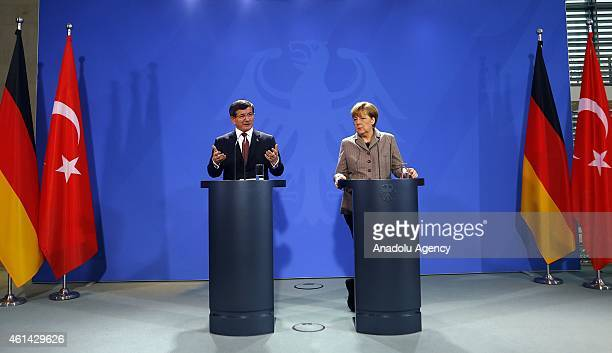 Turkish Prime Minister Ahmet Davutoglu delivers a speech as German Chancellor Angela Merkel listens to him during a joint press conference held after...