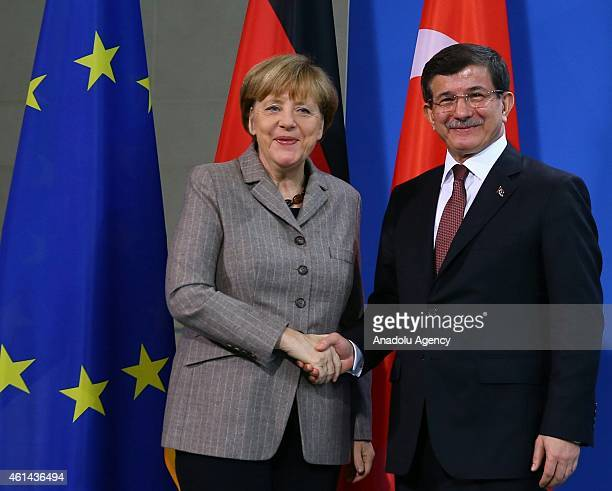 Turkish Prime Minister Ahmet Davutoglu shakes hand with German Chancellor Angela Merkel during a joint press conference held after talks at the...