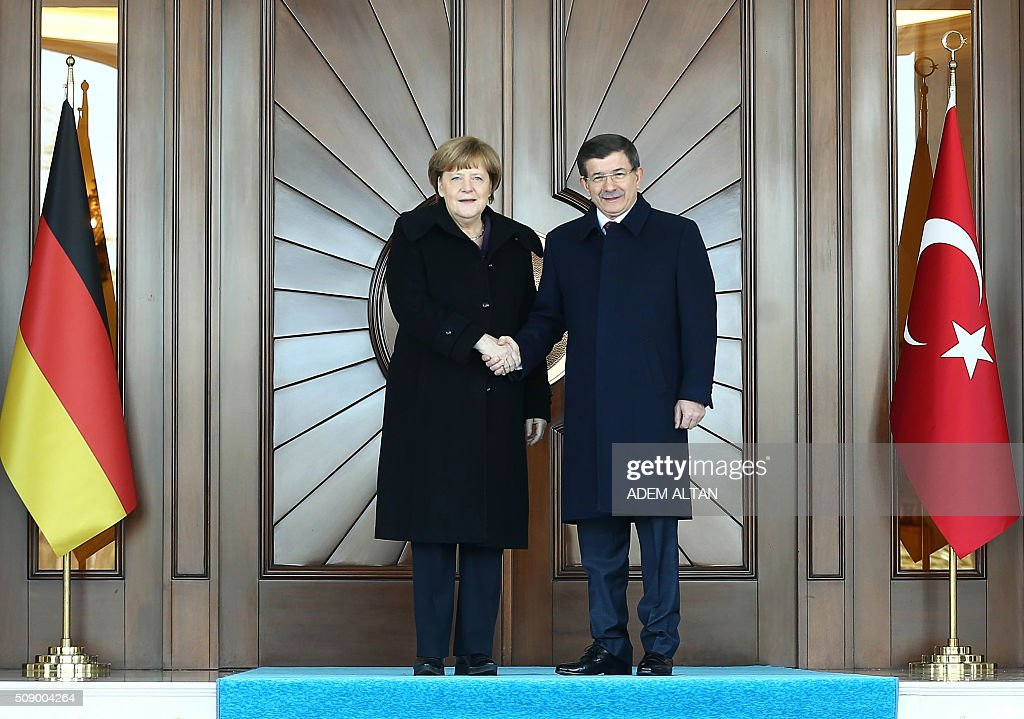 Turkish Prime Minister Ahmet Davutoglu (R) shakes hands with German Chancellor Angela Merkel during her welcoming ceremony in Ankara on February 8, 2016. Merkel is to hold talks with Turkey's President Recep Tayyip Erdogan and Prime Minister Ahmet Davutoglu to press Turkey to strengthen border controls to stem the flow of migrants and refugees heading for Europe. / AFP / ADEM ALTAN