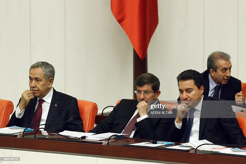 Turkish Prime Minister Ahmet Davutoglu (C), Turkey's Deputy Prime Minister <a gi-track='captionPersonalityLinkClicked' href=/galleries/search?phrase=Ali+Babacan&family=editorial&specificpeople=612964 ng-click='$event.stopPropagation()'>Ali Babacan</a> (R) and Turkey's Deputy Prime Minister Bulent Arinc (L) sit in the Parliament as lawmakers debate the government's budget for 2015 in Ankara, on December 10, 2014.