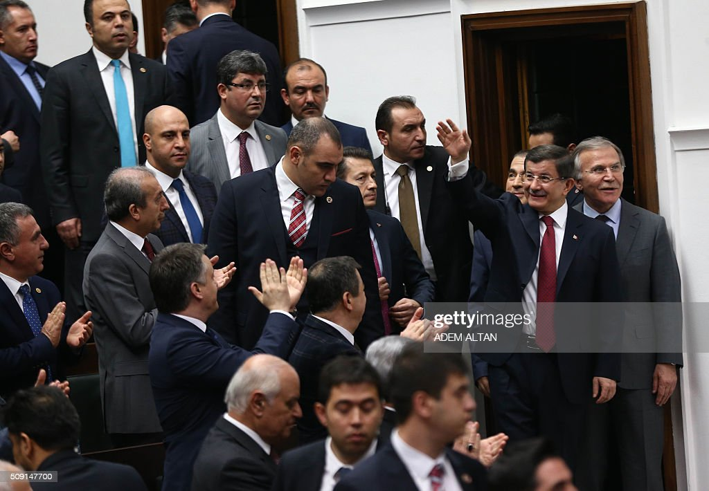 Turkish Prime Minister and leader of the Justice and Development Party (AK Party) Ahmet Davutoglu (2nd R) gestures as he arrives to take part in the AK Party's group meeting at the Grand National Assembly of Turkey (TBMM) in Ankara on February 9, 2016. / AFP / ADEM ALTAN