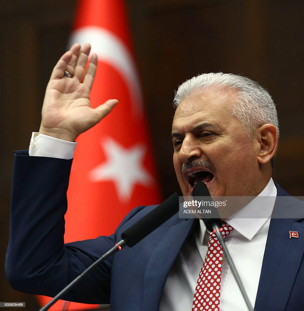 Turkish Prime Minister and leader of Turkey's ruling party Justice and Development Party (AKP) Binali Yildrim gestures as he speaks during an AKP meeting at the Grand National Assembly of Turkey (TBMM) in Ankara, on May 24, 2016. Turkey's incoming Prime Minister Binali Yildirim on May 24 unveiled his new cabinet line-up two days after being given a mandate by President Recep Tayyip Erdogan, with most key ministers keeping their jobs but the EU minister switched. / AFP / ADEM