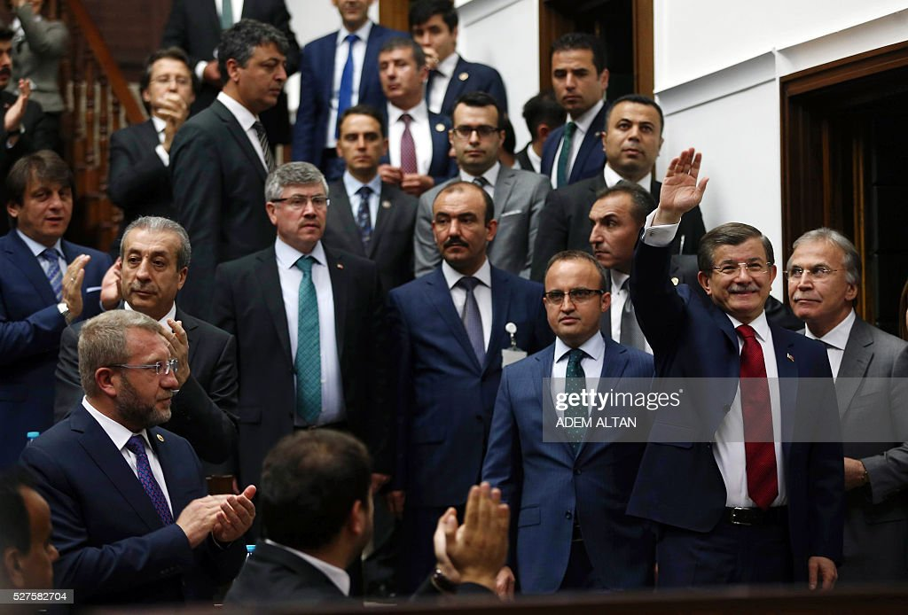 Turkish Prime Minister and leader of Turkey's ruling party, the Justice and Development Party (AKP) Ahmet Davutoglu (C) greets members of parliament of AKP as he arrives for an AKP group meeting at the Turkish parliament in Ankara, on May 03, 2016. / AFP / ADEM