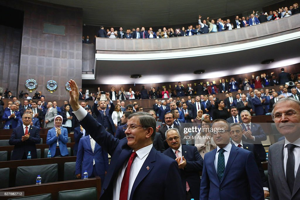Turkish Prime Minister and leader of Turkey's ruling party, the Justice and Development Party (AKP) Ahmet Davutoglu (L) greets members of parliament of AKP as he arrives for a meeting at the Turkish parliament in Ankara in Ankara, on May 03, 2016. / AFP / ADEM