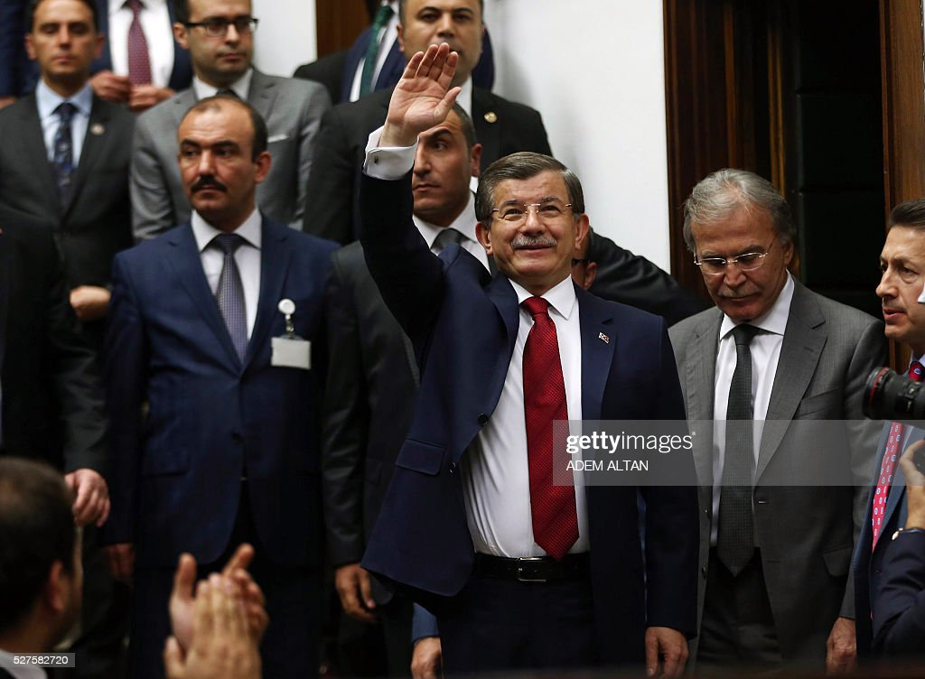 Turkish Prime Minister and leader of Turkey's ruling party, the Justice and Development Party (AKP) Ahmet Davutoglu (C) greets members of parliament of AKP as he arrives for an AKP meeting at the Turkish parliament in Ankara, on May 03, 2016. / AFP / ADEM