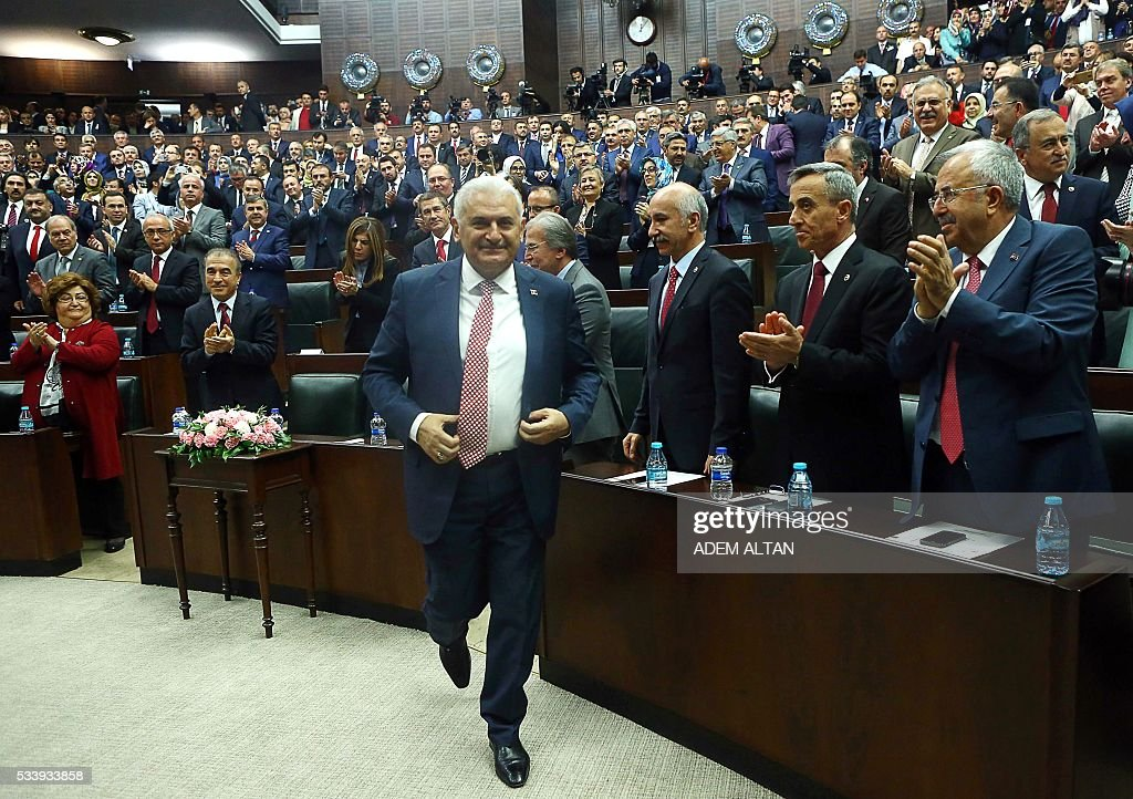 Turkish Prime Minister and the leader of Turkey's ruling party, the Justice and Development Party (AK Party) Binali Yildrim (C) is applauded as he attends the AK Party's group meeting at the Grand National Assembly of Turkey (TBMM) in Ankara, on May 24, 2016. / AFP / ADEM