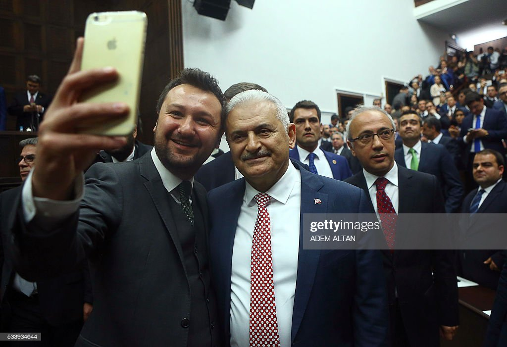 Turkish Prime Minister and the leader of Turkey's ruling party, the Justice and Development Party (AK Party) Binali Yildirim (R) poses for a photo during an AK Party's group meeting at the Grand National Assembly of Turkey (TBMM) in Ankara on May 24, 2016. / AFP / ADEM
