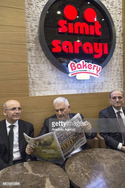 Turkish Prime Minister Binali Yildirim accompanied by Deputy PM Hayati Yazici reads a newspaper at a traditional Turkish bagel bakery in London...