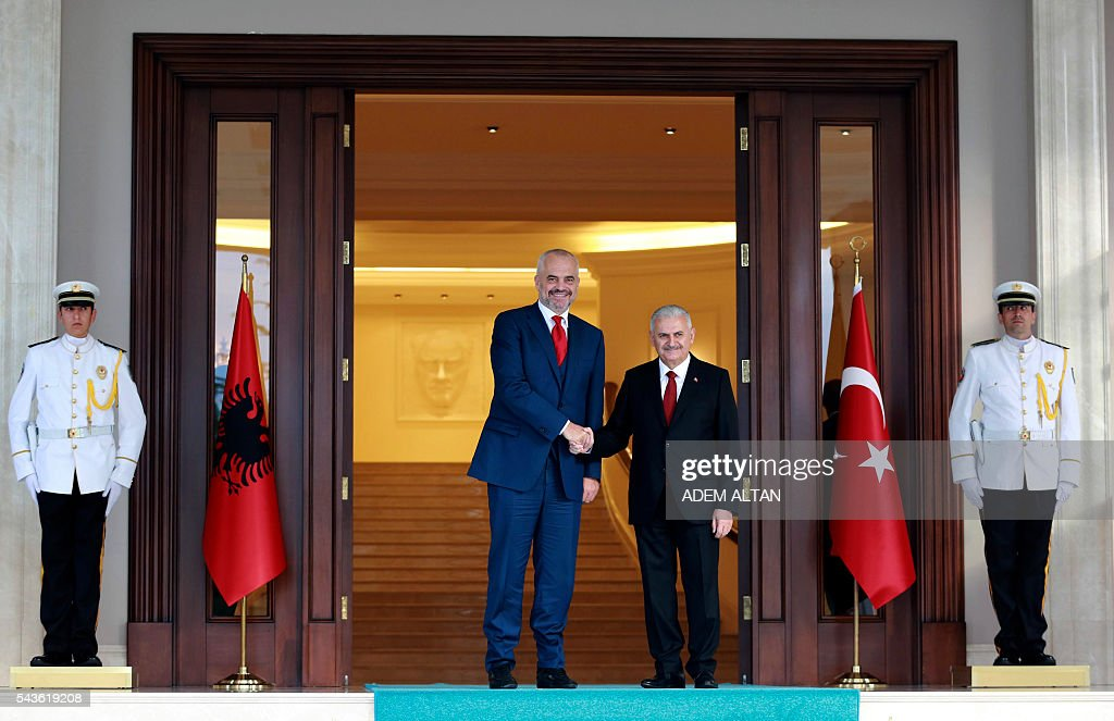 Turkish Prime Minister Binali Yildirim (R) and Albanian Prime Minister Edi Rama (L) shake hands prior to a meeting at Cankaya Palace in Ankara, on June 29, 2016. / AFP / ADEM