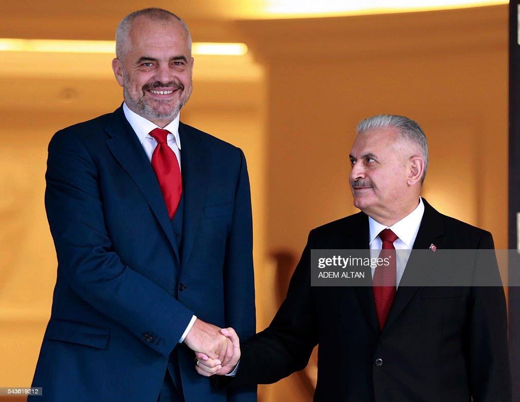 Turkish Prime Minister Binali Yildirim (R) and Albanian Prime Minister Edi Rama (L) shake hands prior to a meeting at Cankaya Palace in Ankara, on June 29, 2016. / AFP / ADEM