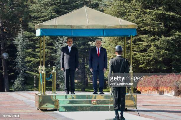 Turkish Prime Minister Binali Yildirim and Iranian First Vice President Eshaq Jahangiri stand at attention in front of a honor guard during a...